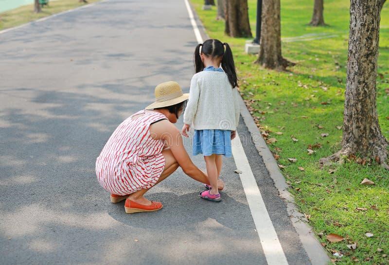 Ασιατική μητέρα που βοηθά την λίγη κόρη για να βάλει τα παπούτσια στο δρόμο υπαίθριο στοκ εικόνα