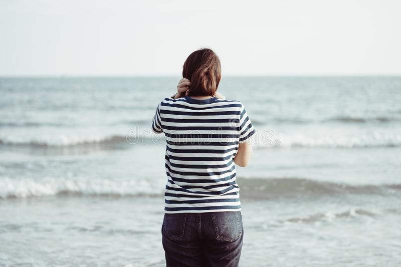 Ασιατική νέα γυναίκα που στέκεται αντιμετωπίζοντας τη θάλασσα Αισθαμένος την πραγματικά μόνη, πληγωμένη θάλασσα όπως έναν βρεφικό στοκ φωτογραφίες
