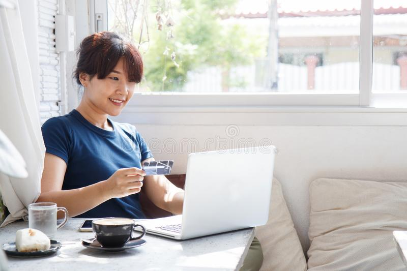 Ασιατική νέα πιστωτική κάρτα εκμετάλλευσης γυναικών και χρησιμοποίηση του φορητού προσωπικού υπολογιστή στοκ εικόνα με δικαίωμα ελεύθερης χρήσης