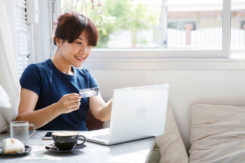 Ασιατική νέα πιστωτική κάρτα εκμετάλλευσης γυναικών και χρησιμοποίηση του φορητού προσωπικού υπολογιστή στοκ εικόνες με δικαίωμα ελεύθερης χρήσης