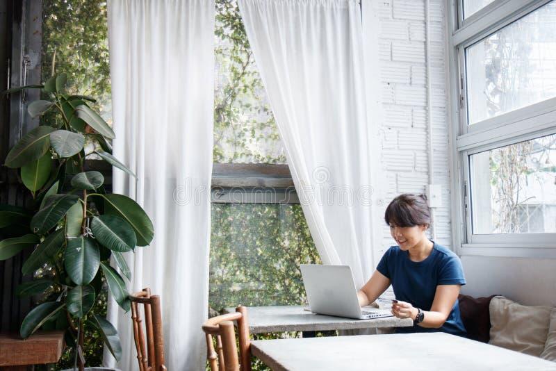 Ασιατική νέα πιστωτική κάρτα εκμετάλλευσης γυναικών και χρησιμοποίηση του φορητού προσωπικού υπολογιστή στοκ φωτογραφία