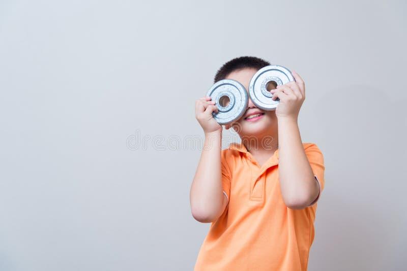 Ασιατική να αστειευτεί αγοριών χειρονομία τα πλαστά γυαλιά που γίνονται που φορά με το σίδηρο dum στοκ εικόνα