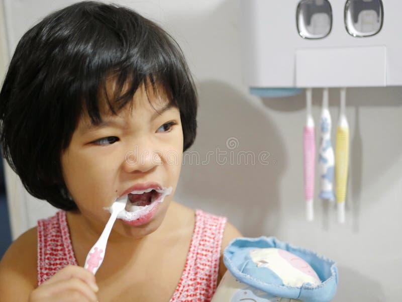 Ασιατική οδοντόβουρτσα εκμετάλλευσης κοριτσάκι Llittle και βούρτσισμα των δοντιών της από μόνη της στοκ εικόνα με δικαίωμα ελεύθερης χρήσης