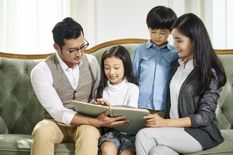 Ασιατική οικογένεια με δύο παιδιά που διαβάζουν το βιβλίο από κοινού στοκ εικόνα