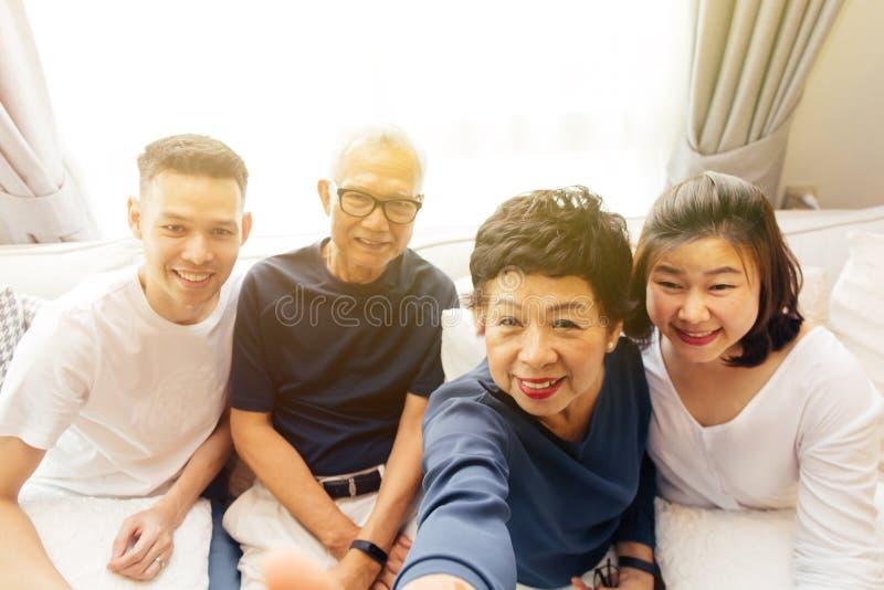 Ασιατική οικογένεια με τα ενήλικα παιδιά και τους ανώτερους γονείς που παίρνουν selfie και που κάθονται σε έναν καναπέ στο σπίτι στοκ εικόνα