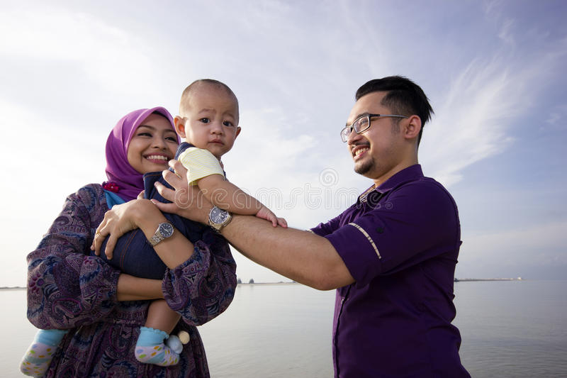 Ασιατική οικογένεια που απολαμβάνει τον ποιοτικό χρόνο στην παραλία στοκ εικόνες