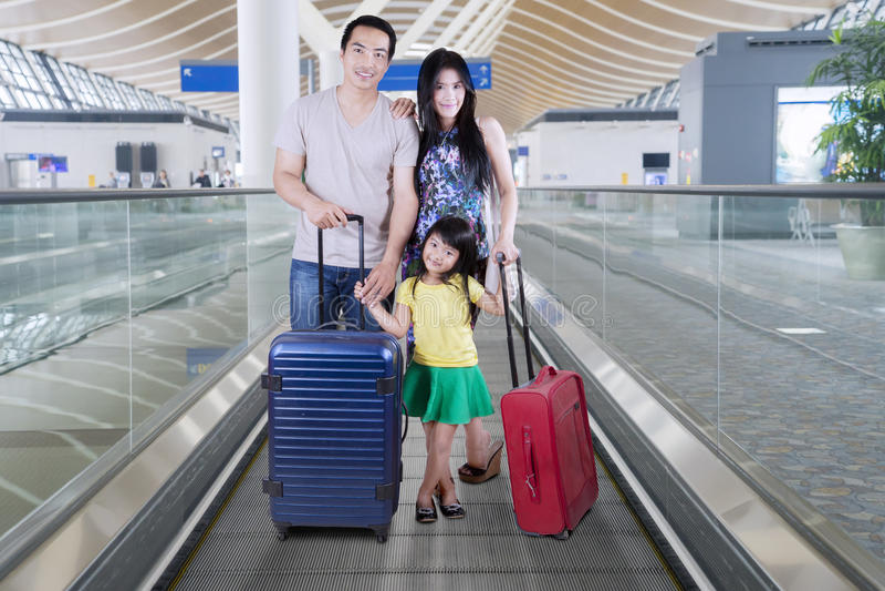 Ασιατική οικογένεια που στέκεται με τις βαλίτσες στην κυλιόμενη σκάλα στοκ φωτογραφίες με δικαίωμα ελεύθερης χρήσης