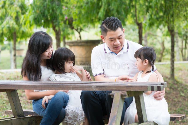 Ασιατική οικογένεια υπαίθρια με το κενό επιτραπέζιο διάστημα στοκ εικόνες