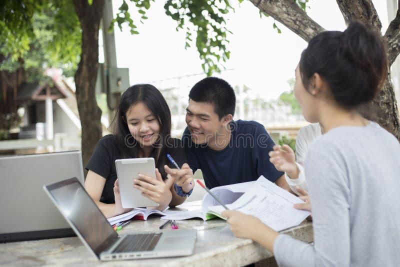 Ασιατική ομάδα σπουδαστών που χρησιμοποιούν την ταμπλέτα και το σημειωματάριο που μοιράζονται με το τ στοκ εικόνες