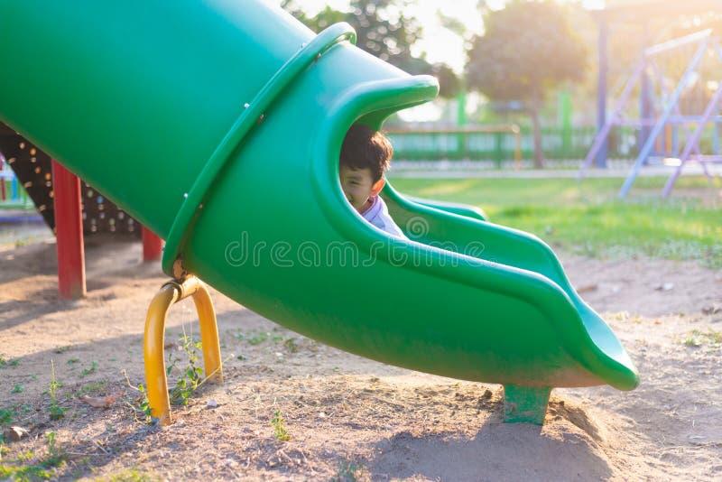 Ασιατική παίζοντας φωτογραφική διαφάνεια παιδιών στην παιδική χαρά κάτω από το φως του ήλιου το καλοκαίρι, ευτυχές παιδί στον παι στοκ εικόνα