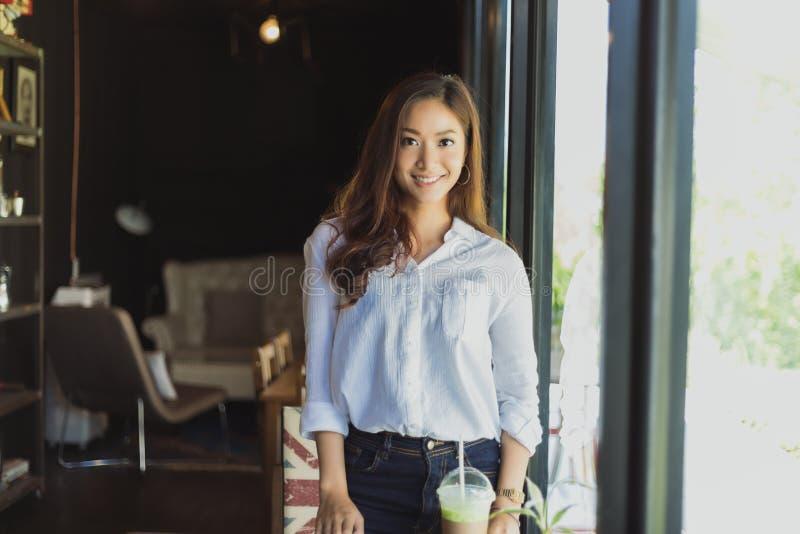 Ασιατική στάση γυναικών χαμογελώντας και ευτυχής χαλαρώνοντας σε μια καφετερία στοκ φωτογραφία