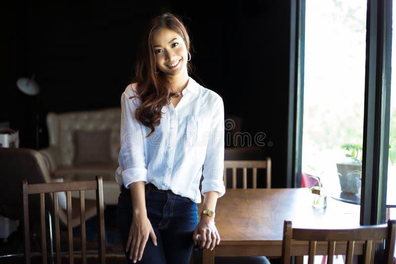 Ασιατική στάση γυναικών χαμογελώντας και ευτυχής χαλαρώνοντας σε μια καφετερία στοκ φωτογραφίες