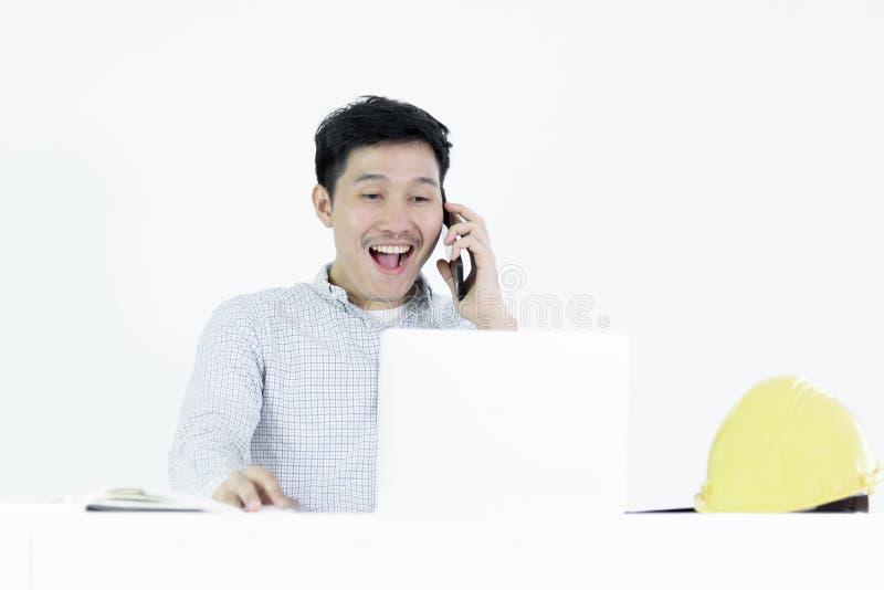 Ασιατική συνεδρίαση ατόμων μισθών μηχανικών υπαλλήλων στο γραφείο και ομιλία με το τηλέφωνο, που απομονώνεται στο άσπρο υπόβαθρο στοκ φωτογραφία με δικαίωμα ελεύθερης χρήσης