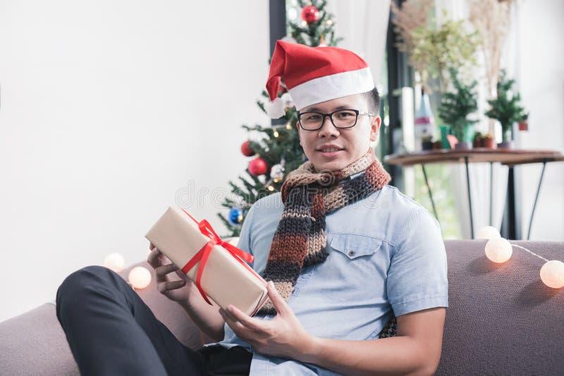 Ασιατική συνεδρίαση ατόμων στο κιβώτιο δώρων εκμετάλλευσης καναπέδων, έννοια ημέρας των Χριστουγέννων στοκ εικόνα με δικαίωμα ελεύθερης χρήσης