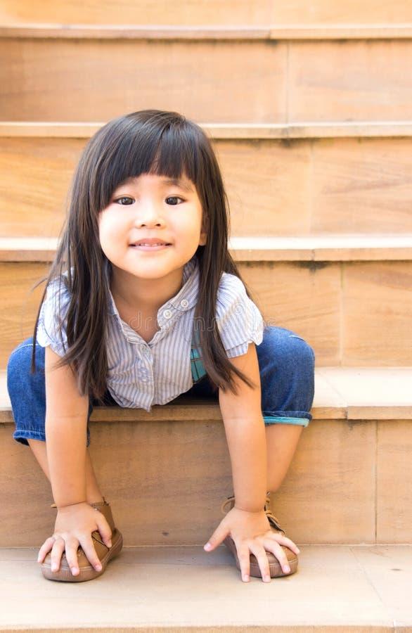 ασιατική συνεδρίαση χαμόγελου κοριτσιών στα κίτρινα σκαλοπάτια στοκ εικόνες