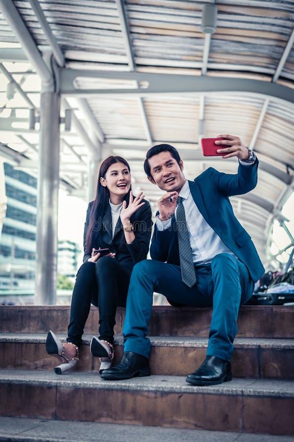 Ασιατική τηλεοπτική κλήση επιχειρηματιών και επιχειρηματιών στο φίλο τους από το smartphone στοκ εικόνες
