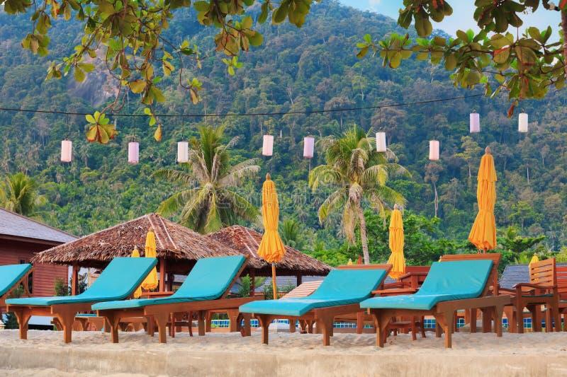 Ασιατική τροπική παραλία με τα sunbeds κάτω από τα δέντρα, Ταϊλάνδη στοκ φωτογραφία