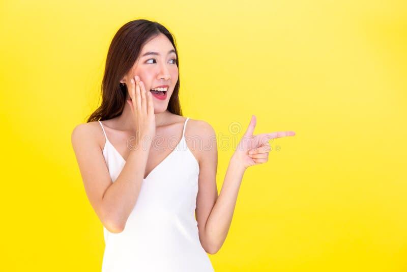 Ασιατική όμορφη γυναίκα που εκπλήσσεται και που συγκλονίζεται με το χαμόγελο και υπόδειξη στο κενό διάστημα αντιγράφων στοκ φωτογραφία με δικαίωμα ελεύθερης χρήσης