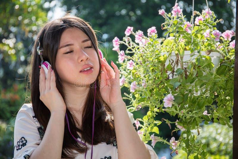 Ασιατική όμορφη νέα γυναίκα που φορά τα ακουστικά στον κήπο στοκ φωτογραφίες με δικαίωμα ελεύθερης χρήσης