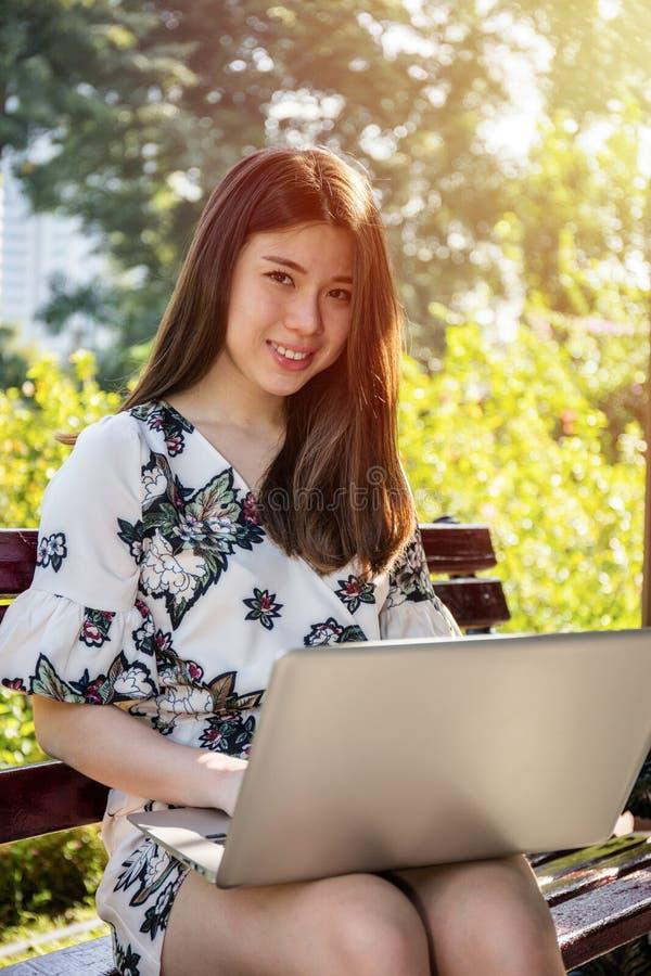 Ασιατική όμορφη νέα συνεδρίαση γυναικών στον πάγκο με το lap-top στοκ φωτογραφία