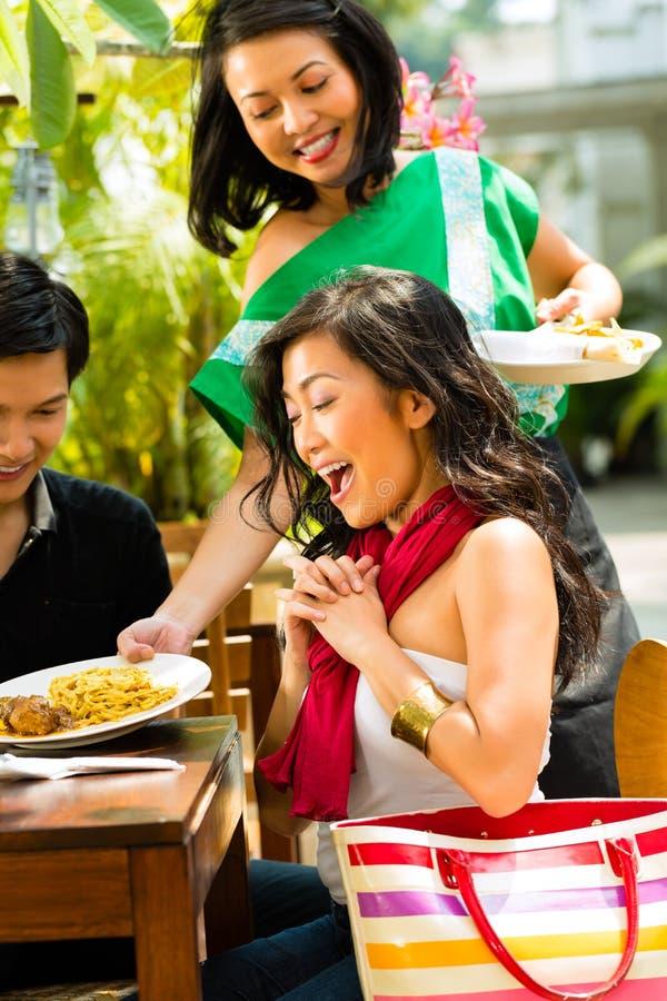 Ασιατικοί άνδρας και γυναίκα στο εστιατόριο στοκ φωτογραφία