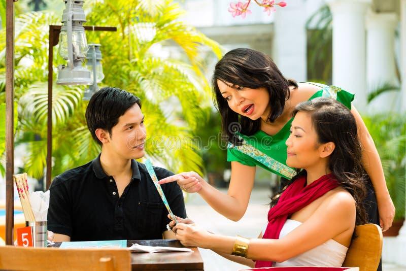 Ασιατικοί άνδρας και γυναίκα στο εστιατόριο στοκ εικόνες