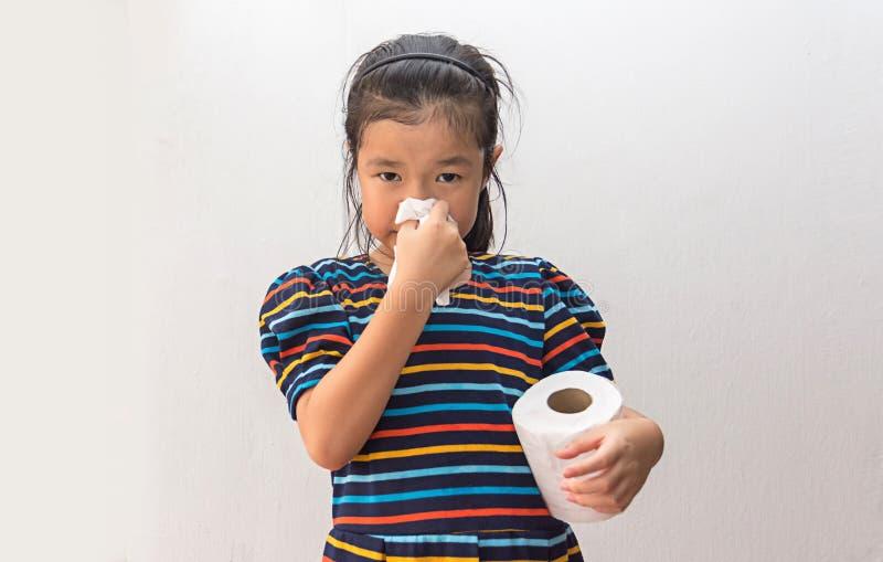 Ασιατικοί άρρωστοι κοριτσιών με το φτέρνισμα στη μύτη και τον κρύο βήχα σε χαρτί ιστού στοκ εικόνα