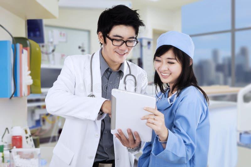 Ασιατικοί γιατροί με την ταμπλέτα στην κλινική στοκ εικόνα με δικαίωμα ελεύθερης χρήσης