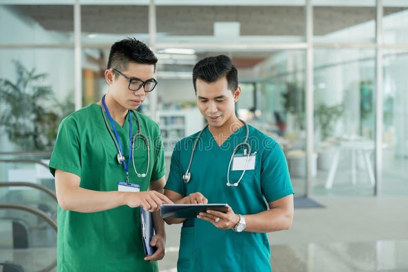 Ασιατικοί γιατροί που χρησιμοποιούν την ταμπλέτα στο νοσοκομείο στοκ φωτογραφία