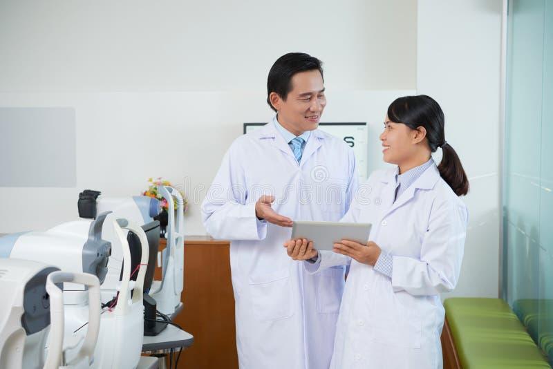 Ασιατικοί γιατροί Coworking που χρησιμοποιούν την ταμπλέτα στοκ εικόνα