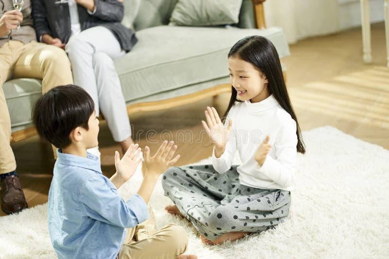 Ασιατικοί γονείς και δύο παιδιά που διαβάζουν το βιβλίο από κοινού στοκ φωτογραφία με δικαίωμα ελεύθερης χρήσης