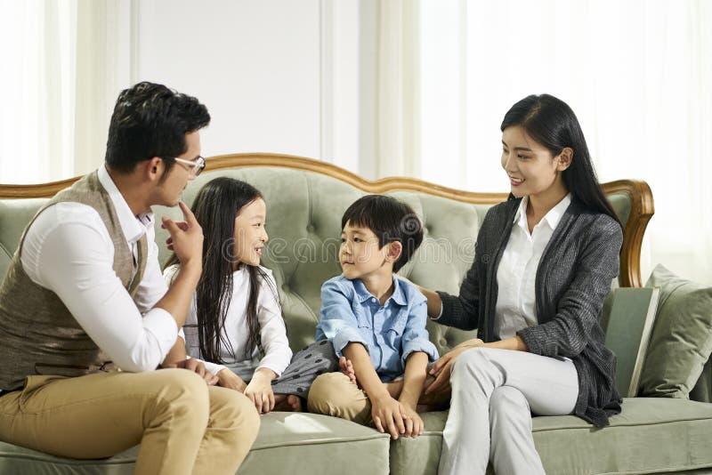 Ασιατικοί γονείς και δύο παιδιά που κουβεντιάζουν στο σπίτι στοκ εικόνες