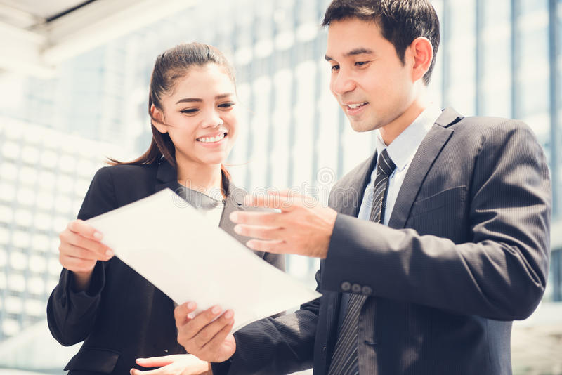 Ασιατικοί επιχειρηματίας και επιχειρηματίας που συζητούν το έγγραφο στοκ φωτογραφίες
