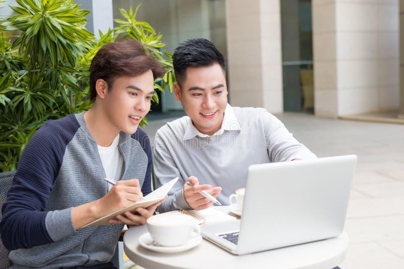 Ασιατικοί επιχειρηματίες με το περιστασιακό κοστούμι που λειτουργεί στη καφετερία στοκ φωτογραφίες με δικαίωμα ελεύθερης χρήσης
