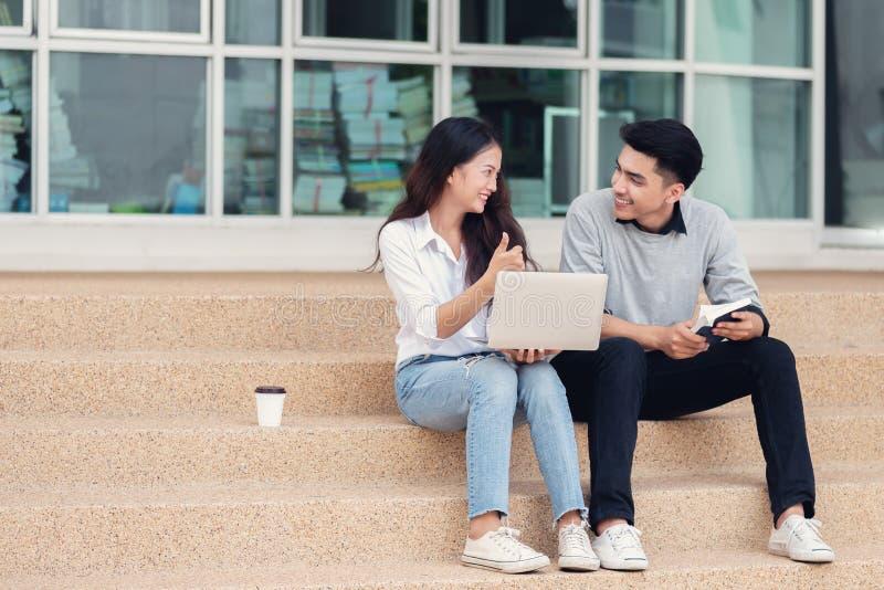 Ασιατικοί σπουδαστές ή συνάδελφοι ζευγών που κάθονται στα σκαλοπάτια και το s στοκ φωτογραφίες