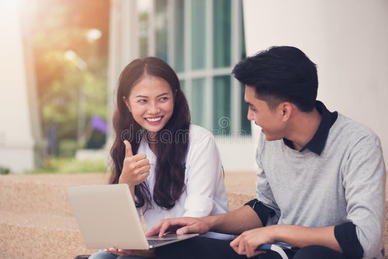 Ασιατικοί σπουδαστές ή συνάδελφοι ζευγών που κάθονται στα σκαλοπάτια και το s στοκ εικόνες
