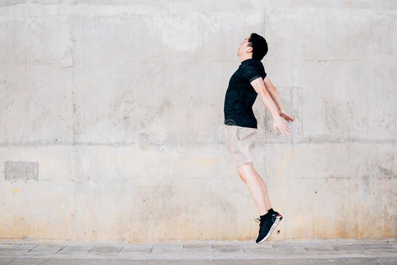 Ασιατικός αθλητικός τύπος που πηδά ενάντια στον τοίχο στοκ εικόνα με δικαίωμα ελεύθερης χρήσης