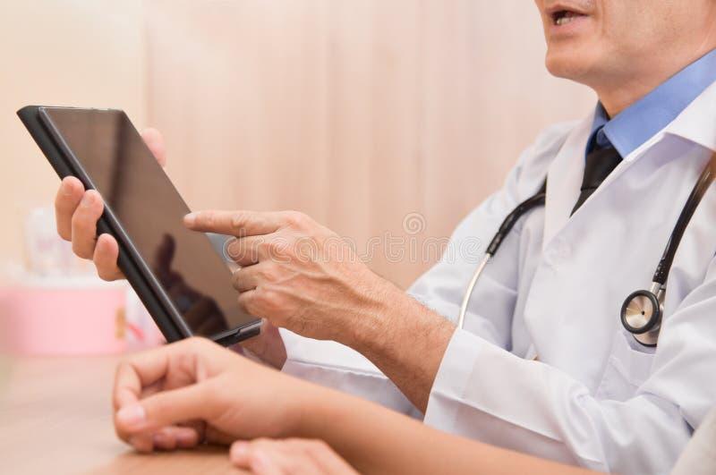 Ασιατικός αρσενικός γιατρός που χρησιμοποιεί τον ψηφιακό υπολογιστή ταμπλετών στοκ εικόνες