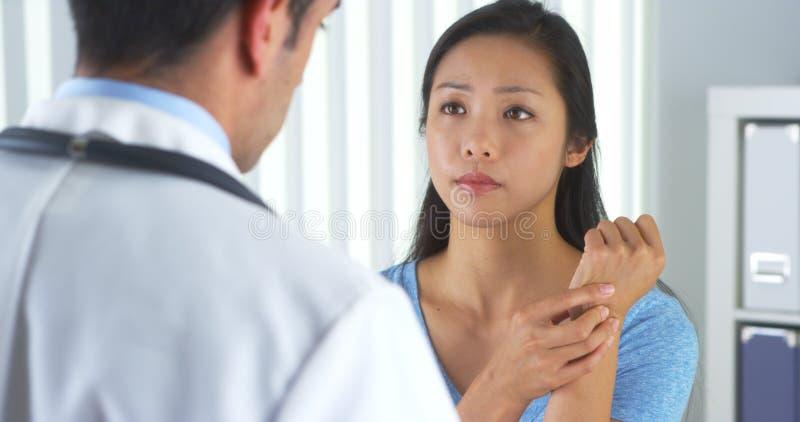 Ασιατικός ασθενής που περιγράφει τον πόνο καρπών στο γιατρό στοκ φωτογραφία με δικαίωμα ελεύθερης χρήσης