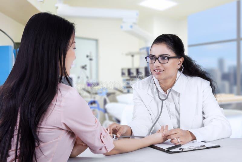 Ασιατικός γιατρός που ακούει ο υπομονετικός κτύπος της καρδιάς στοκ εικόνα με δικαίωμα ελεύθερης χρήσης