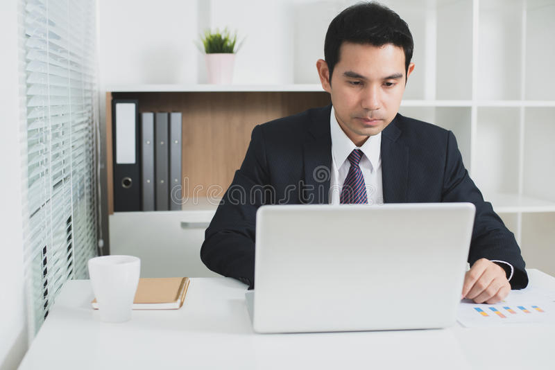 Ασιατικός επιχειρηματίας που επικεντρώνεται στη χρησιμοποίηση του φορητού προσωπικού υπολογιστή στοκ εικόνα με δικαίωμα ελεύθερης χρήσης