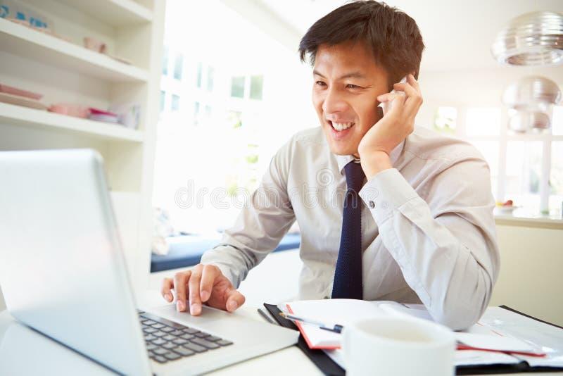 Ασιατικός επιχειρηματίας που εργάζεται από το σπίτι που χρησιμοποιεί το κινητό τηλέφωνο στοκ εικόνα