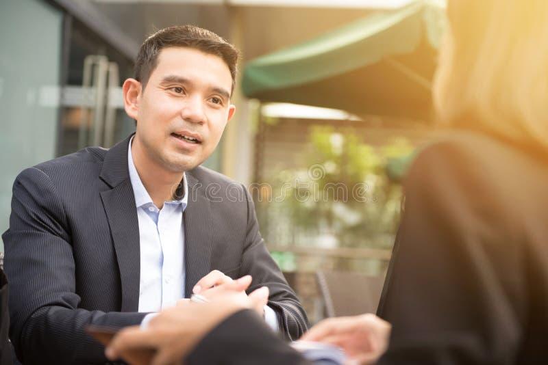 Ασιατικός επιχειρηματίας που μιλά με μια επιχειρηματία στοκ εικόνες