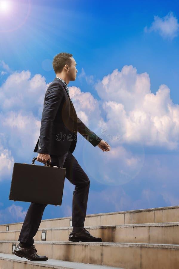 Ασιατικός επιχειρηματίας που περπατά επάνω τα σκαλοπάτια για να βρεί την επιτυχία Concepti στοκ φωτογραφίες