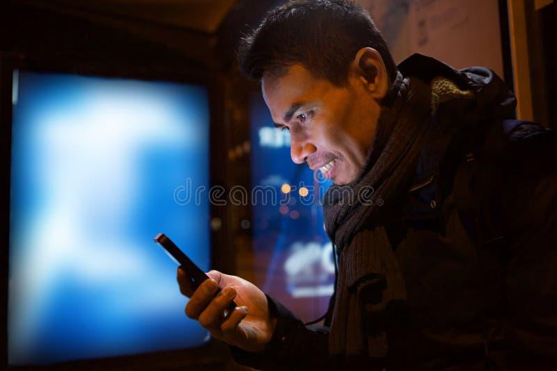 Ασιατικός ηληκιωμένος με το smartphone τη νύχτα στην πόλη στοκ εικόνες