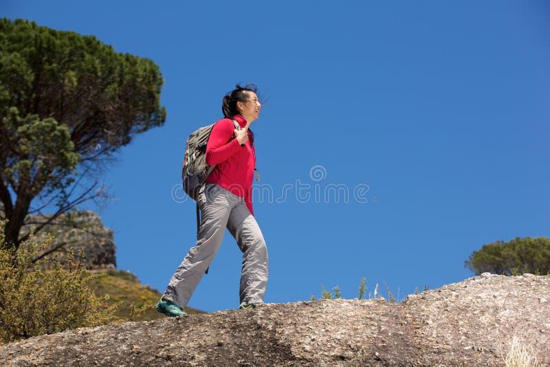 Ασιατικός θηλυκός οδοιπόρος που περπατά πέρα από τον απότομο βράχο με το σακίδιο πλάτης στοκ εικόνα