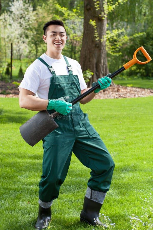 Ασιατικός κηπουρός που έχει τη διασκέδαση στον κήπο στοκ φωτογραφία