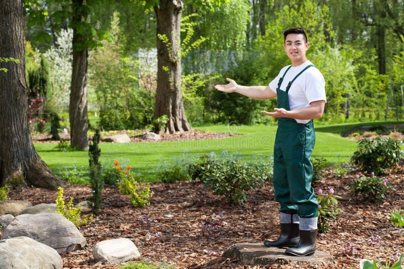 Ασιατικός κηπουρός που παρουσιάζει τον όμορφο κήπο στοκ φωτογραφία με δικαίωμα ελεύθερης χρήσης