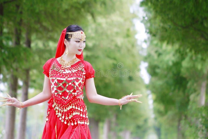 Ασιατικός κινεζικός χορευτής κοιλιών ομορφιάς στο κόκκινο φόρεμα με το πέπλο στοκ φωτογραφίες