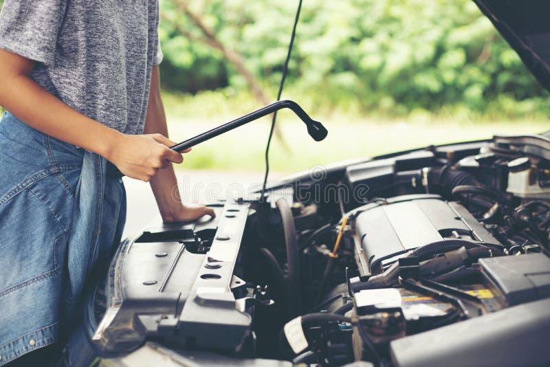 Ασιατικός μηχανικός γυναικών που κρατά ένα γαλλικό κλειδί διαθέσιμο, προετοιμασμένος για τα αυτοκίνητα επισκευών στο δρόμο στοκ φωτογραφία